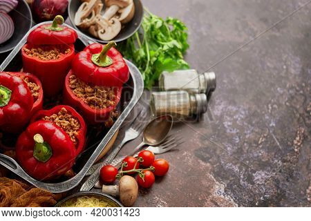 Red bell stuffed paprika peppers in iron cooking pot with various ingredients on side