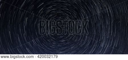 Stellar Trails, The Rotation Of Bright Stars At Night Around The Polar Star Against A Blue Sky And A