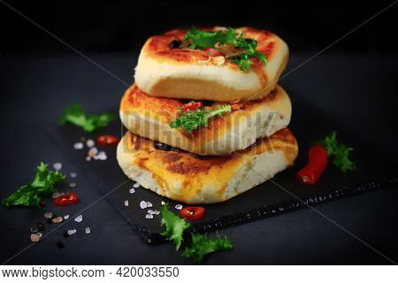 Delicious Homemade Mini Pizzas On A Black Background. Mini Pizzas In A Column.