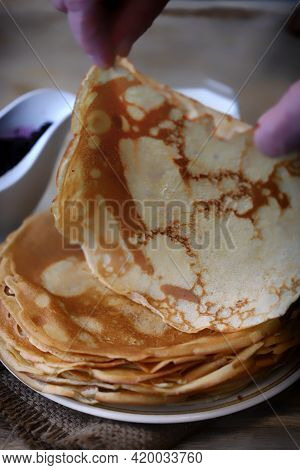 A Stack Of Pancakes. A Hand Takes A Pancake From A Plate Of Pancakes. Pancake Week.