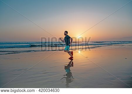 Active Healthy Runner Jogging Outdoor. Young And Active Jogger Running On Beach Sunset.