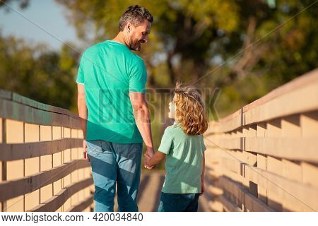 Back View Of Father And Son Walking On Wooded Bridge Outdoor. Father And Son Talking, Having Fun In