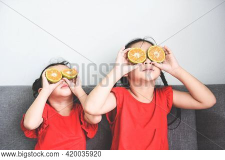 Little Girl Playing With Fresh Mandarin Orange Fruits Child Is Having Fun With Fruit Food For Kids F