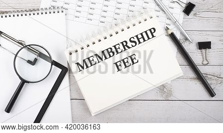Notepad With Text Membership Fee With A Pen,office Tools And Graphs On Desktop.