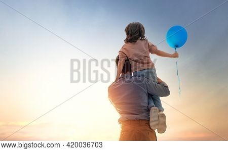 Happy loving family. Father and his daughter child playing and hugging outdoors. Cute little girl and daddy with air balloon.