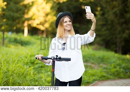 Outdoor Portrait Of Young Beautiful Girl In Black Hat Standing With Her Electric Scooter And Take Se