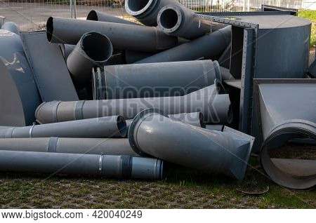 Gray Plastic Pipes Of A Demolished Air Condition System Lying In A Meadow At A Construction Site