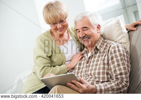 Happy elderly couple talking using tablet computer together at home