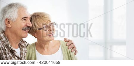 Happy elderly couple hugging at home and smiling.