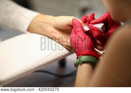 Close-up Of Woman Using Means Of Protection. Manicurist Covering Nails Of Client With Light Nail Pol