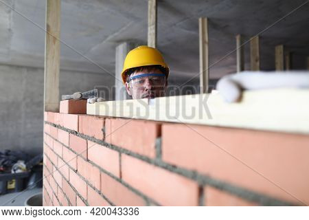 Portrait Of Builder Laying Bricks Using Special Tools. Worker Building Brick Walls