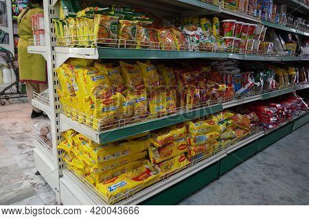 Several Packets Of Packaged Noodles Kept On Shelf For Sale. Maggi Instant Noodles On Display At Supe