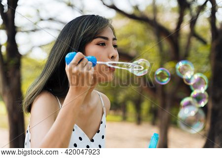 South East Asian Ethnic 20s Woman Blowing Air Bubbles In The Park Young Happy Girl Wears Stylish Dre