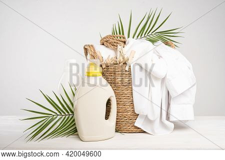 Wicker Basket With White Linen, Clothespins, Clothesline, Washing Gel And Fabric Softener On A White