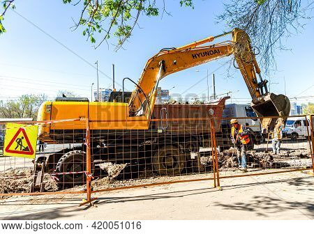 Samara, Russia - May 6, 2021: Backhoe Working On The Construction Of New Road In Summer Day. Heavy M