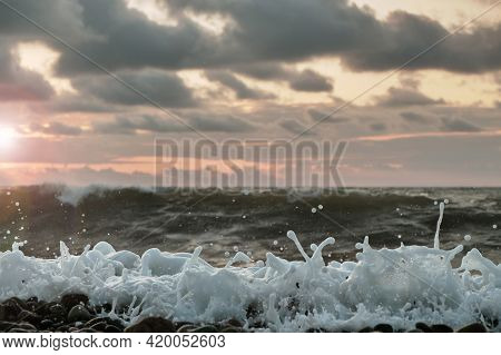 White Foamy Waves Splashing At The Sea With Blurred Sunset Seascape Background