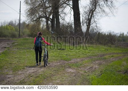 A Girl With A Bicycle Walks A Field Trail. Woman Riding A Mountain Bike In The Forest. Hiker Woman W