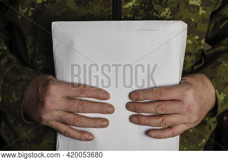 A Military Man Is Holding A Large Mail Package. Sealed Paper Envelope With Documents Inside Against