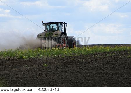 Tractor In A Field Rear View, Tractor With A Plow On An Agricultural Field. Big Green Tractor Workin