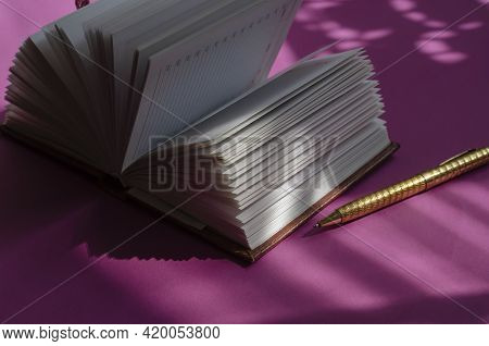 Light And Shadow Composition With An Open Diary On A Pink Table. Blank Pages Of The Notebook. A Gold