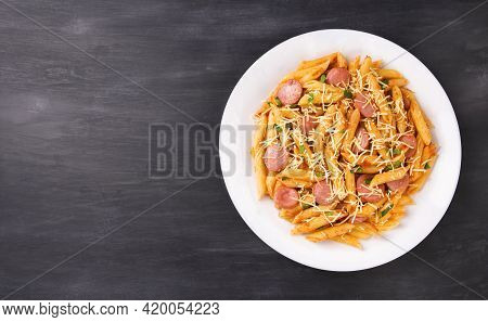 Penne Pasta In Tomato Sauce With Sausages And Cheese, Decorated With Parsley On A  Black Background,