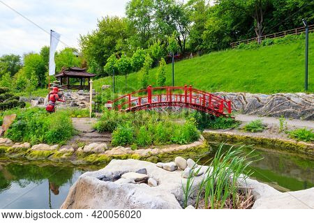 Red Bridge And Gazebo By A Pond In Japanese Garden