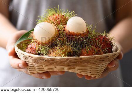 Ripe Rambutan Fruit In A Bamboo Basket Holding By Woman Hand, Rambutan Is Tropical Fruit And Native