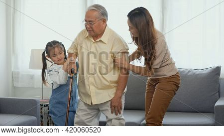 Asian Family, Daughter And Granddaughter Take Care Support Grandfather Who Is Suffering From Knee Pa