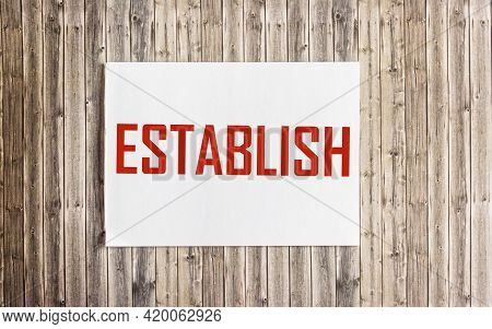 Establish Word Concept On Notepad And On Wooden Table