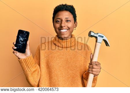 Young african american girl holding broken smartphone showing cracked screen and hammer smiling with a happy and cool smile on face. showing teeth.
