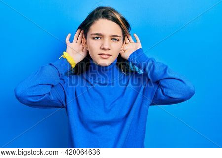 Young brunette girl wearing turtleneck sweater trying to hear both hands on ear gesture, curious for gossip. hearing problem, deaf