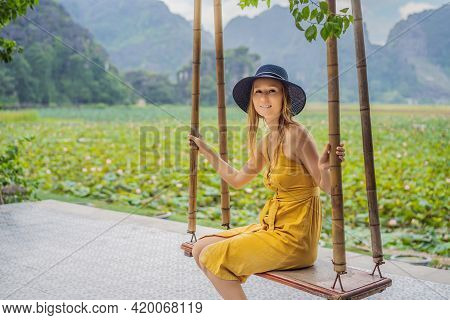 Young Woman Is Swinging On A Swing On The Lotus Field