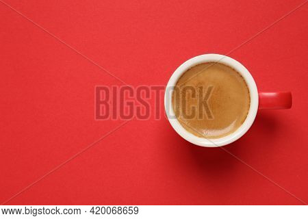 Cup Of Aromatic Coffee On Red Background, Top View. Space For Text
