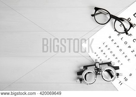 Trial Frame, Eye Chart Test, Glasses And Space For Text On White Wooden Table. Ophthalmologist Tools