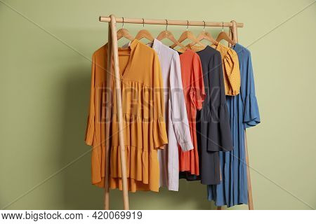 Collection Of Trendy Women's Garments On Rack Near Green Wall. Clothing Rental Service