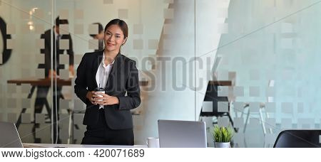Confidence Woman In Black Formal Suit Standing With Holding A Take-away Coffee Cup At The Office Mee