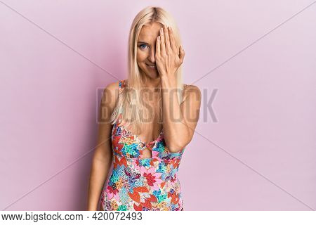 Young blonde woman wearing swimsuit covering one eye with hand, confident smile on face and surprise emotion.