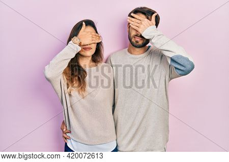 Young hispanic couple wearing casual clothes covering eyes with hand, looking serious and sad. sightless, hiding and rejection concept