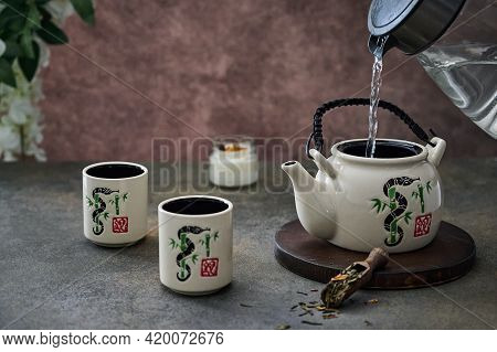 From The Kettle Pour Boiling Water In The Teapot For The Tea Ceremony With An Old Ceramic Service. S