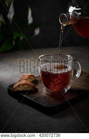 Black Tea Is Poured From The Teapot Into Transparent Cup With Bubbles. Nearby Cookies On Cutting Boa