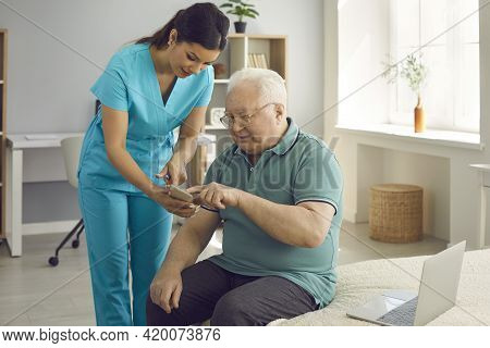 Healthcare Worker Teaching Her Senior Patient To Use Health App On His Mobile Phone