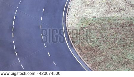 Fragment Of An Asphalt Ring Road With White Road Markings