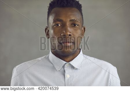 Studio Portrait Of Serious Young African-american Man In White Shirt Looking At Camera