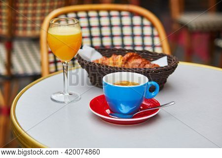 Cup Of Fresh Hot Coffee, Orange Juice And Traditional French Croissant On Table Of Parisian Outdoor