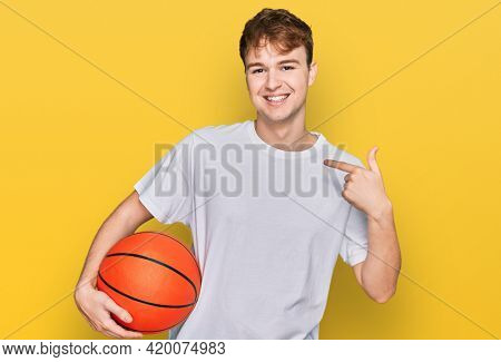 Young caucasian man holding basketball ball pointing finger to one self smiling happy and proud