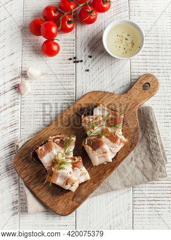 Ukrainian Lard, Pork Lard, Sprinkled With Fresh Chopped Herbs On A Wooden Board. Copy Space.