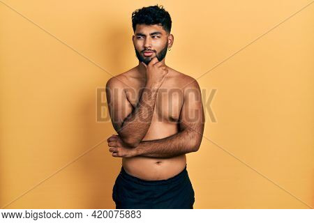 Arab man with beard wearing swimwear shirtless with hand on chin thinking about question, pensive expression. smiling with thoughtful face. doubt concept.