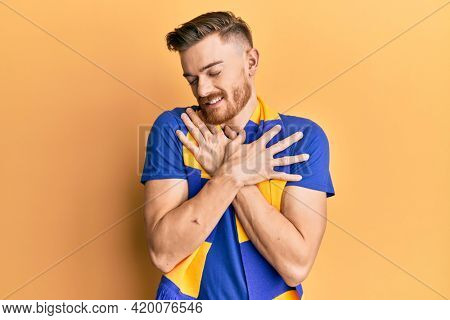 Young redhead man football hooligan cheering game hugging oneself happy and positive, smiling confident. self love and self care