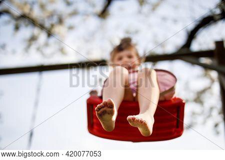 Closeup Of Feet Of Little Toddler Girl Having Fun On Swing In Domestic Garden. Small Child Swinging