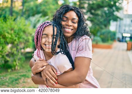 Beautiful african american mother and daughter smiling happy and hugging. Standing with smile on face standing at the park.